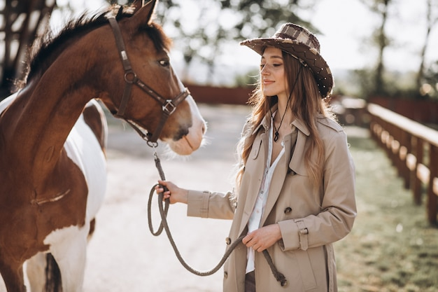 Joven mujer feliz con caballo en el rancho