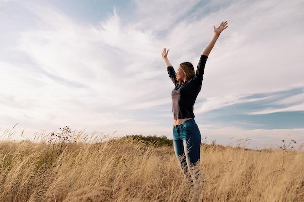 Joven mujer feliz en un campo de oro en puesta de sol.