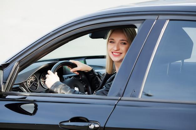 Joven mujer feliz compró nuevo coche moderno.