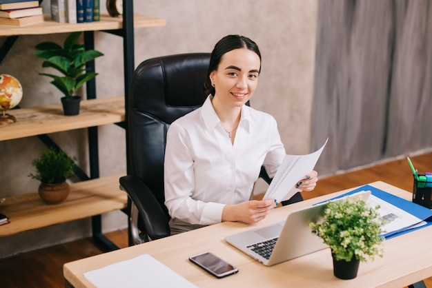 Joven mujer feliz con documentos en la oficina