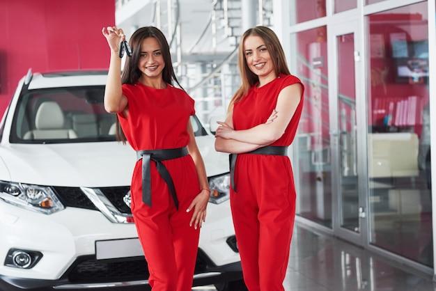 Joven mujer feliz dos cerca del coche con llaves en mano - concepto de comprar coche.