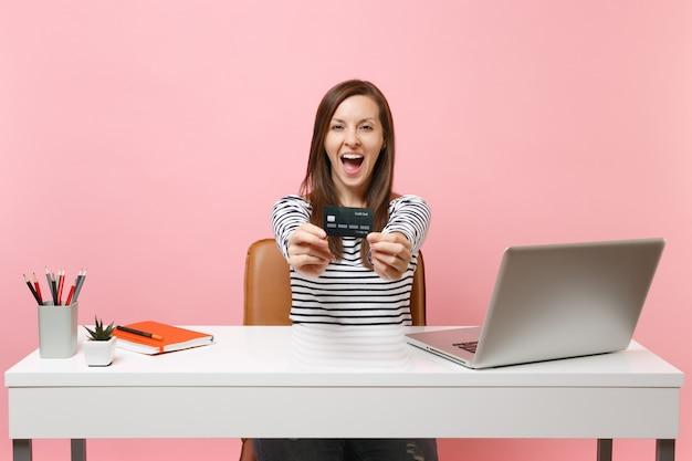 Joven mujer feliz emocionada mantenga la tarjeta de crédito mientras se sienta, trabaja en la oficina en el escritorio blanco con ordenador portátil