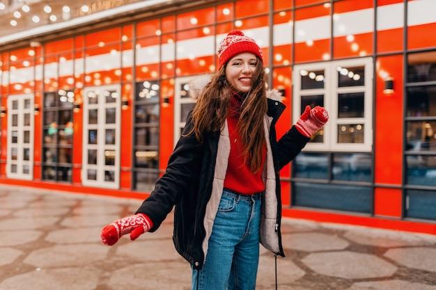 Joven mujer feliz emocionada muy sonriente en guantes rojos y gorro de punto con abrigo de invierno caminando en la calle de navidad de la ciudad, tendencia de moda de estilo de ropa de abrigo