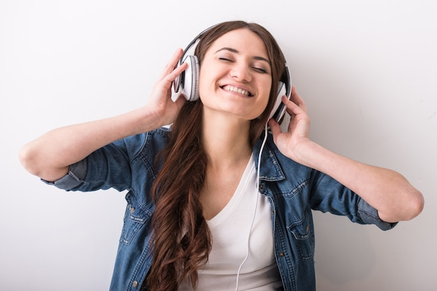 Joven mujer feliz está escuchando música con auriculares.