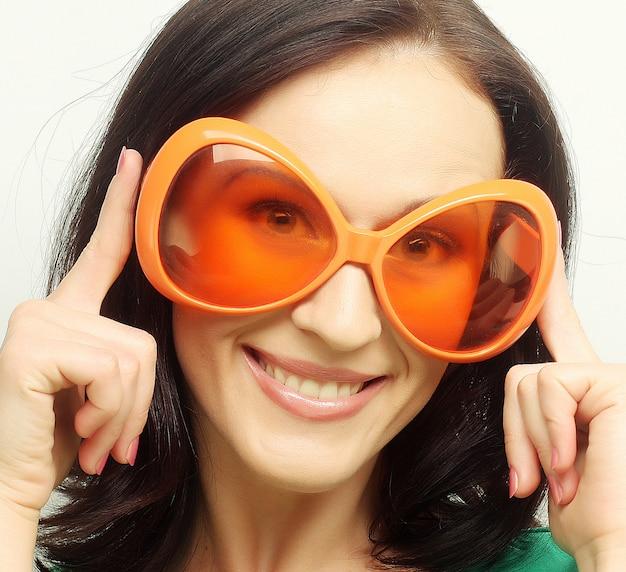 Joven mujer feliz con grandes gafas de sol naranjas