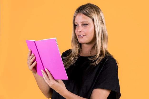Joven mujer feliz leyendo libro sobre fondo amarillo