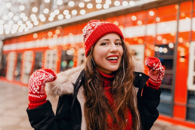 Joven mujer feliz muy sonriente en guantes rojos y gorro de punto con abrigo de invierno caminando en las calles de la ciudad, ropa de abrigo