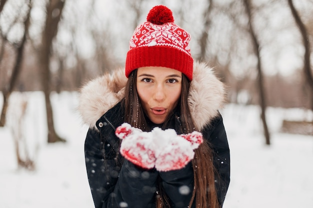 Joven mujer feliz muy sonriente en guantes rojos y gorro de punto con abrigo de invierno, caminando en el parque, jugando con nieve en ropa de abrigo