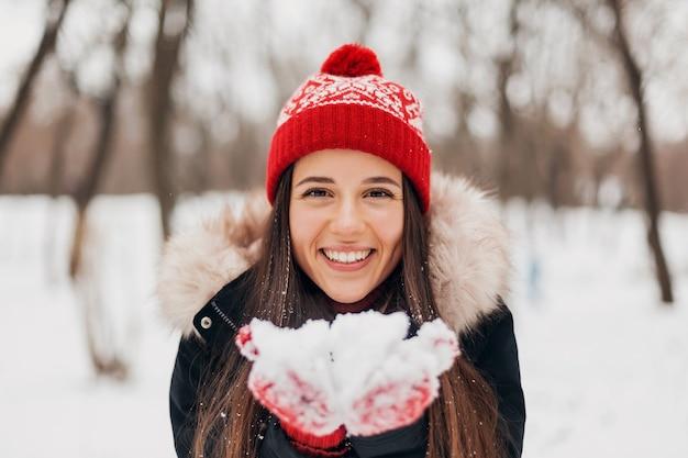 Joven mujer feliz muy sonriente en guantes rojos y gorro de punto vistiendo abrigo de invierno, caminando en el parque, soplando nieve