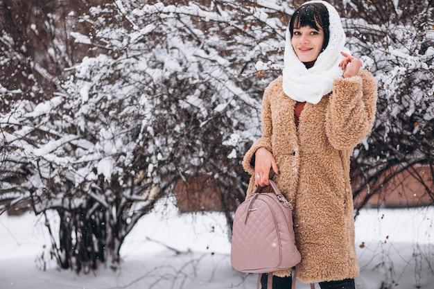 Joven mujer feliz en paños calientes en un parque de invierno