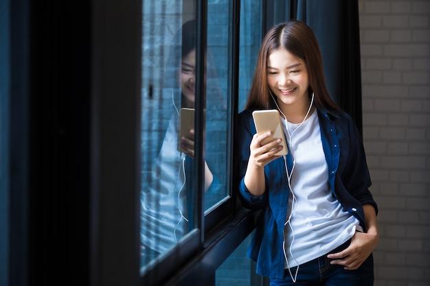 Joven mujer feliz de pie en la ventana grande escuchando música en su teléfono