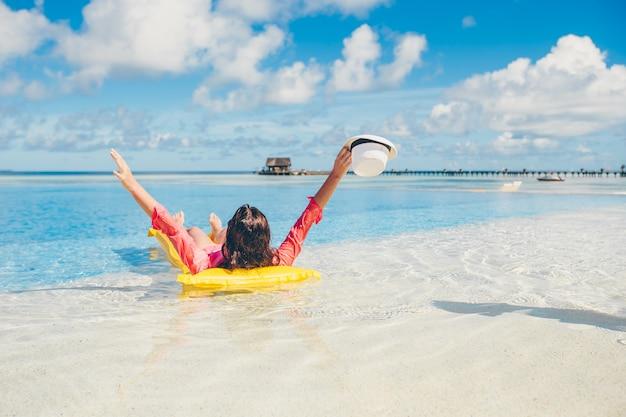 Joven mujer feliz relajante en una piscina