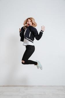 Joven mujer feliz saltando y celebrando el éxito