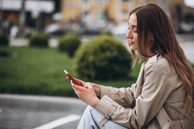 Joven mujer feliz sentada en el parque y hablando por teléfono