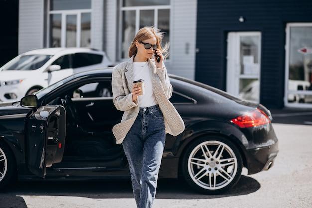 Joven mujer feliz tomando café en el coche