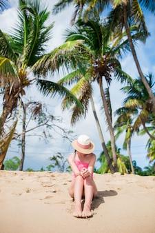 Joven mujer feliz en traje de baño en playa blanca