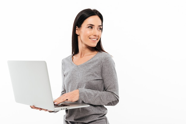 Joven mujer feliz usando la computadora portátil.