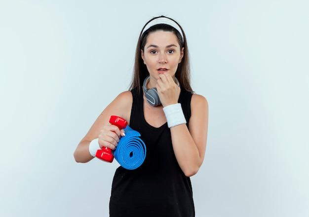 Joven mujer fitness en diadema con auriculares sosteniendo mancuernas y colchoneta de yoga sorprendido de pie sobre la pared blanca