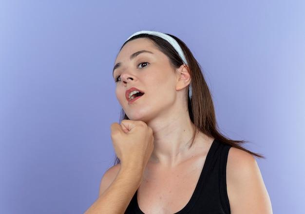 Joven mujer fitness en diadema siendo perforada en su cara sobre la pared azul