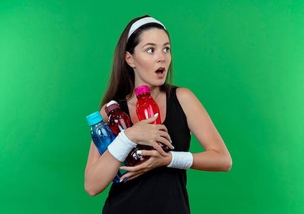 Joven mujer fitness en diadema sosteniendo botellas de agua mirando a un lado con expresión de miedo de pie sobre la pared verde