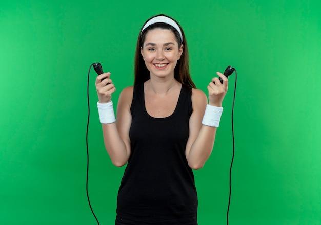 Joven mujer fitness en diadema sosteniendo saltar la cuerda sonriendo alegremente va a saltar de pie sobre la pared verde