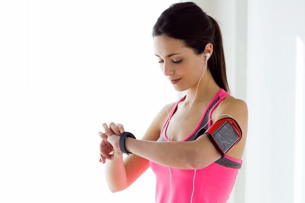 Joven mujer de fitness mirando su reloj inteligente mientras toma un descanso.