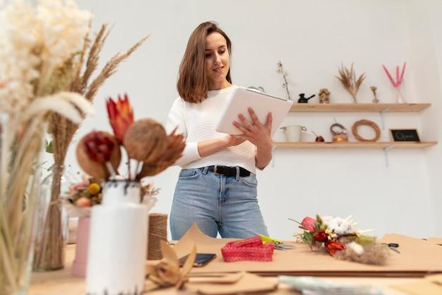 Joven mujer florista leyendo desde un portapapeles
