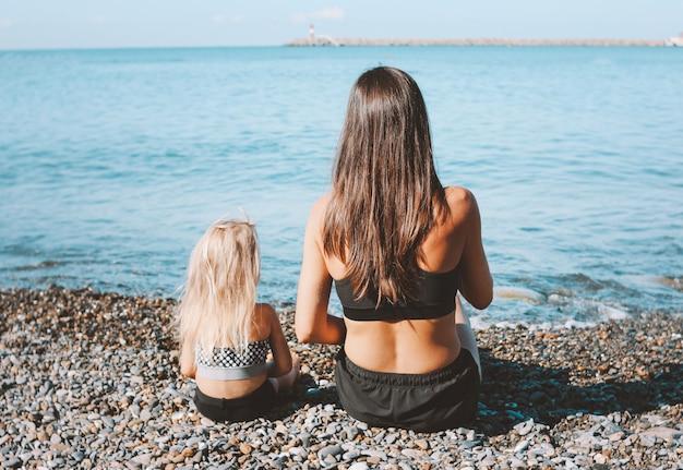 Joven mujer en forma mamá con linda niña sentada en la playa juntos