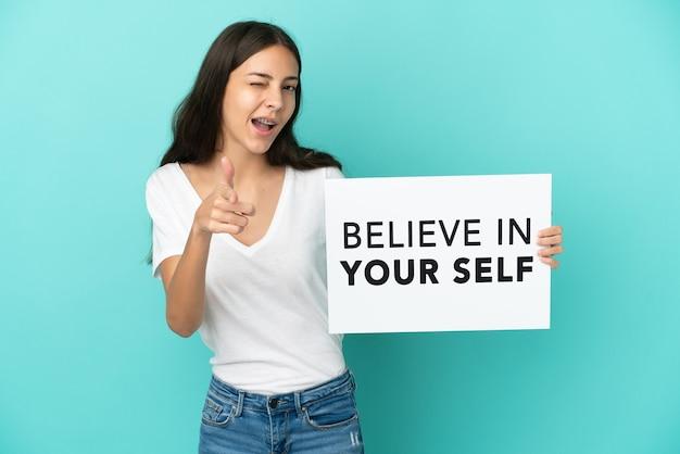 Joven mujer francesa aislada sobre fondo azul sosteniendo un cartel con el texto cree en ti mismo y apuntando hacia el frente