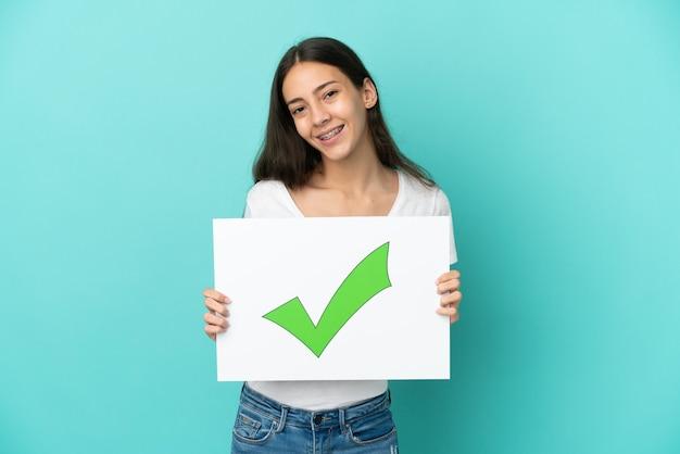 Joven mujer francesa aislada sobre fondo azul sosteniendo un cartel con texto icono de marca de verificación verde con expresión feliz