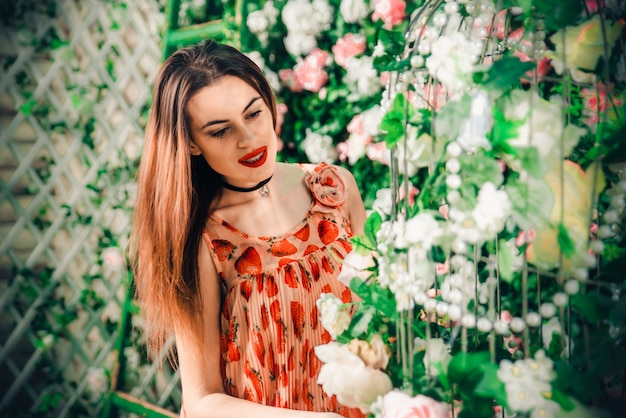 Joven mujer frente a su hermosa casa de flores