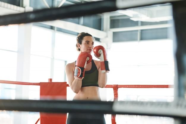 Joven mujer fuerte dispuesta a luchar contra su rival de pie en el ring de boxeo con las manos delante de ella