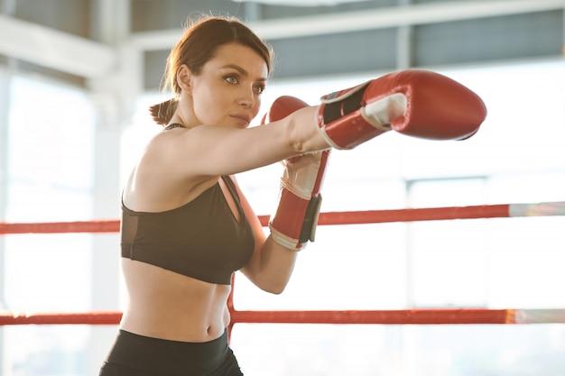 Joven mujer fuerte en ropa deportiva y guantes de boxeo entrenando golpes de ataque mientras está de pie en el ring