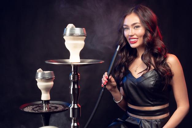 Joven mujer fumando una cachimba en la oscuridad