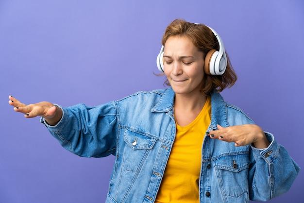 Joven mujer georgiana aislada en la pared púrpura escuchando música y bailando