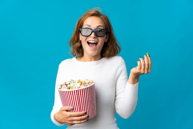 Joven mujer georgiana aislada sobre fondo azul con gafas 3d y sosteniendo un gran balde de palomitas de maíz