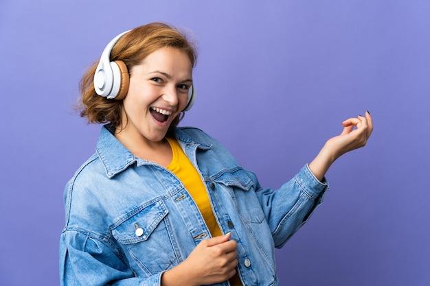 Joven mujer georgiana aislada sobre fondo púrpura escuchando música y haciendo gesto de guitarra