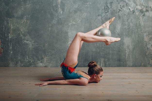 Joven mujer gimnasta profesional baila gimnasia rítmica con pelota en el estudio