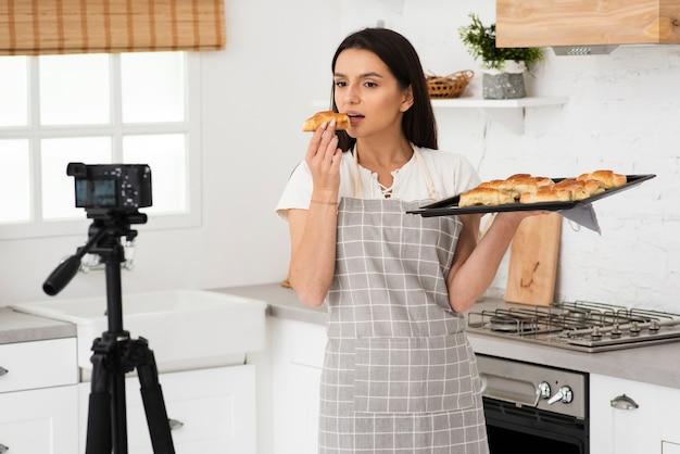 Joven mujer grabando mientras cocina