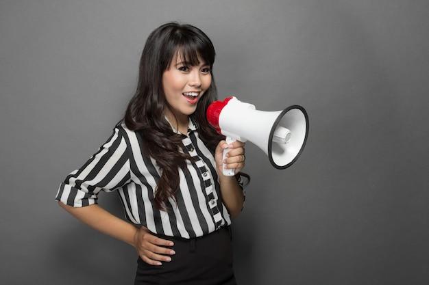 Joven mujer gritando con un megáfono