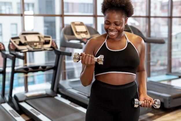 Joven mujer haciendo ejercicio con pesas