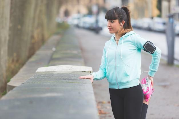 Joven mujer haciendo ejercicios de estiramiento antes de trotar.