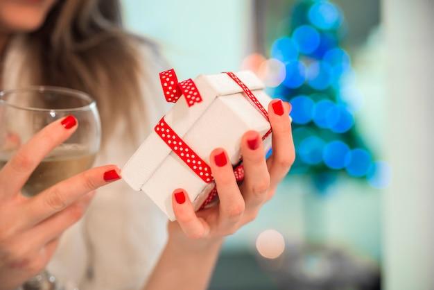 Joven mujer hermosa celebración chrismtas presente en sus manos delante de un árbol de navidad bellamente decorado.