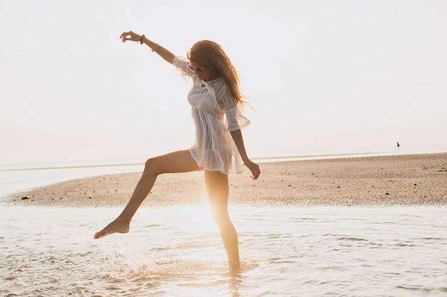 Joven mujer hermosa delgada en la playa al atardecer