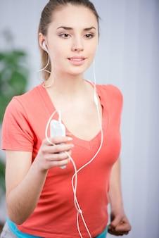 Joven mujer hermosa escuchando música y ofertas de fitness.
