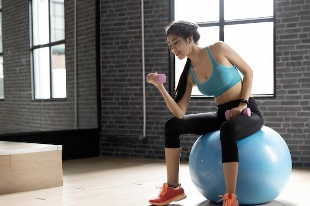 Joven mujer hermosa haciendo ejercicios con pesas en el gimnasio