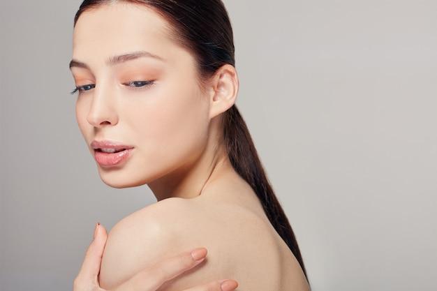 Joven mujer hermosa con ojos azules y labios carnosos tiene una mano sobre su hombro.