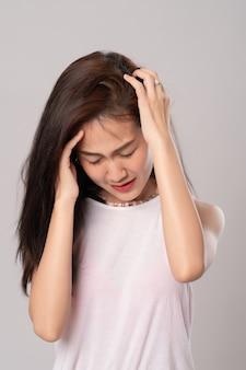 Joven mujer hermosa tiene dolor de cabeza; retrato de mujer de negocios asiáticos grave o migraña, triste, cuidado de la salud y concepto de negocio.