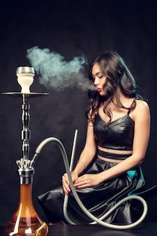 Joven mujer hermosa en vestido negro fumando y exhala cachimba
