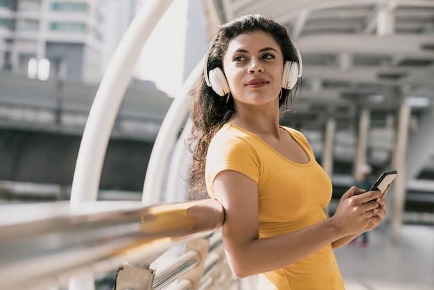 Joven mujer hispana con auriculares bluetooth escuchando música